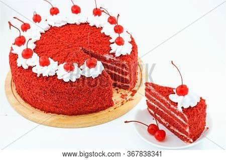 Round Red Velvet Cake On A Wooden Plate Decorated With Canned Cherries And Whipped Cream, A Slice Of