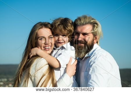 Happy Family Embrace. Family Mother Father And Son Hugging. Son Hugging Parents On Blue Sky. Summer