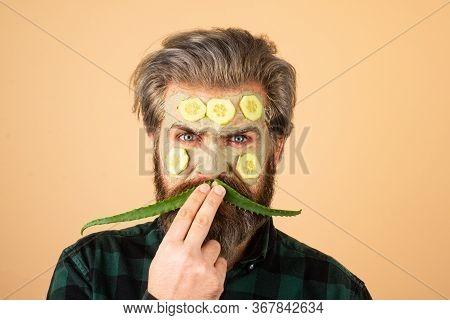 Funny Man With Facial Mask With Cucumber And Aloe Vera Having Fun. Spa Man Applying Facial Clay Mask