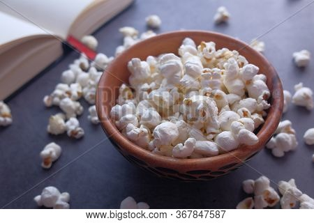 Close Up Of Popcorn In Bowl And Book On Table