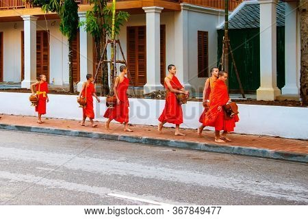 Luang Prabang, Laos - July 27, 2016: Alms Giving In The Morning When Monks Walk By The Streets For T