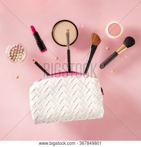 Professional Makeup, Flying Out Of A Bag, On A Pink Background. Lipstick, Brushes, Powder Compact, A
