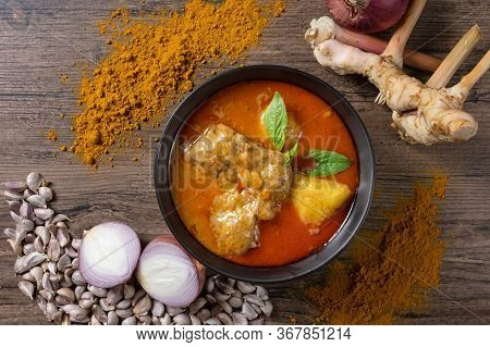 Chicken Massaman Curry In Black Bowl With Herb , Spices And Curry Powder On Wooden Background. Thai