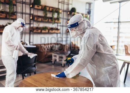 Professional Workers In Hazmat Suits Disinfecting Indoor Of Cafe Or Restaurant, Pandemic Health Risk