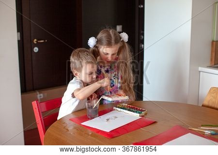 Seven Year Old Girl And Three Year Old Boy Paint In The Kitchen. Modern Home Interior With White Col