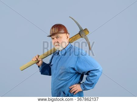 Serious Construction Worker With Pickaxe. Workman With Pick Axe. Male Bricklayer In Hard Hat With Pi