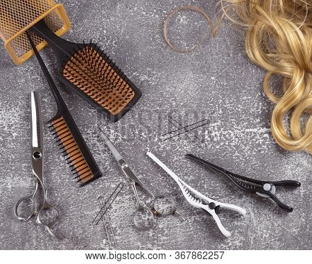 Hairdressing Tools On Gray Background. Golden Curls And Yellow Combs On Flat Lay