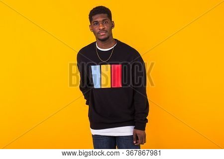 Handsome African American Man Posing In Black Sweatshirt On A Yellow Background. Youth Street Fashio