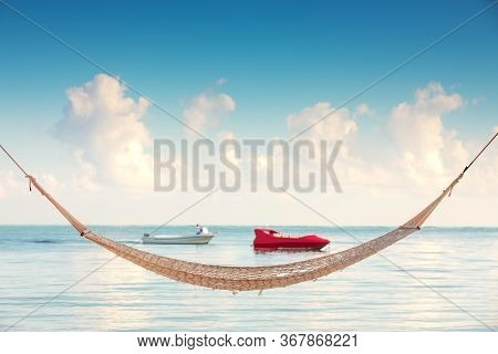 Empty Hammock Under Tall Palm Trees On Tropical Beach And Speed Boat