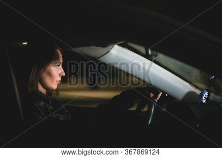 A Young Woman Driver Is Driving Her Car At Night.