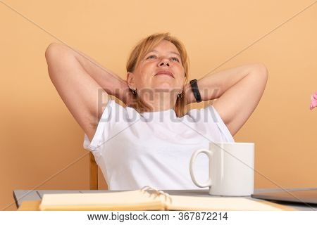 Middle Age Woman In White T-shirt Sitting At The Table, Holds Her Hands Behinde Her Head And Shows H