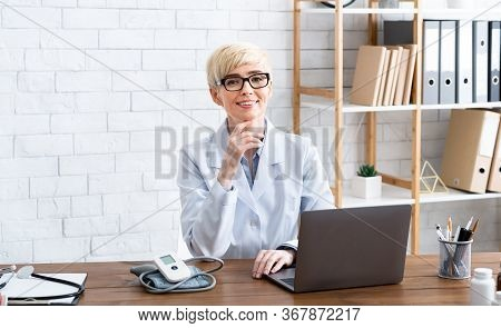 Affordable Treatment. Smiling Woman Doctor Sitting At Table In Interior Of Office