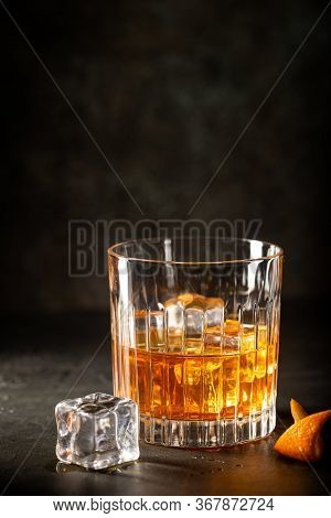 Glass Of Scotch Whiskey With Ice Cubes On Black Background
