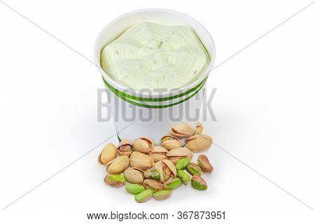 Pistachio Ice Cream In The Paper Cup Among The Pistachio Nuts On A White Background