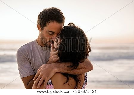 Couple Sharing A Romantic Embrace On A Beach At Dusk
