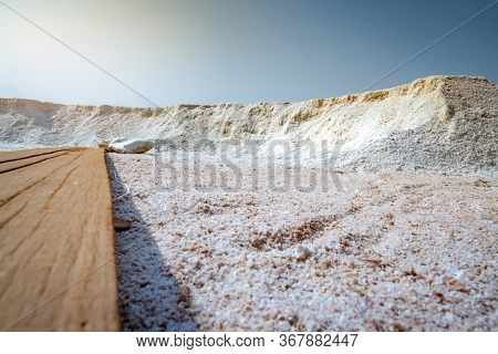 Low Angle View Of Brine Salt Farm With Blue Sky. Pile Of Organic Sea Salt Near Warehouse. Raw Materi