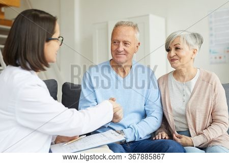 Portrait Of Smiling Senior Couple Shaking Hands With Female Doctor While Visiting Private Clinic