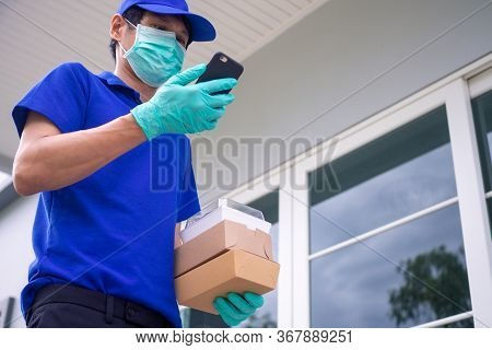 The Male Delivery Staff Standing At The Door Wears A Uniform With A Mask And Gloves Deliver Food Acc