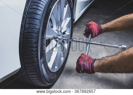 Car Mechanic Hand Using Cross Wrench To Uninstallation The Wheel Nuts For Changing Alloy Wheel Of Ca