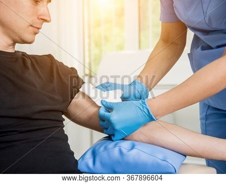 Nurse Dressing Wound For Patients Hand With Burn Injury