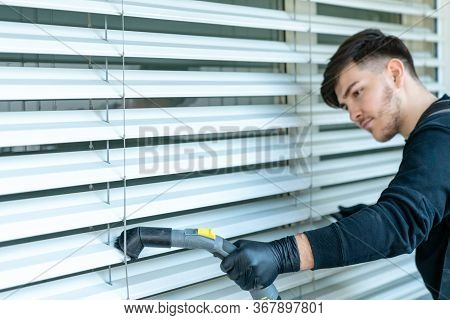 Professional Cleaner Vacuum Cleaning Window Blinds On An Apartment Balcony