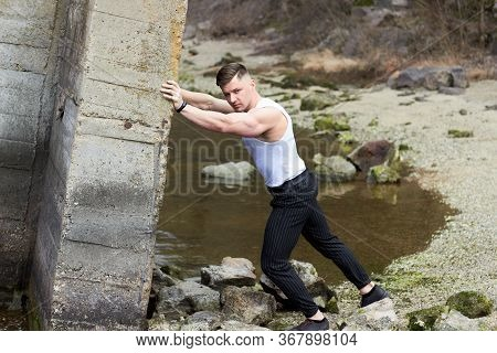 Attractive Young Guy Demonstrates Muscular Torso Outdoors. Beautiful Physique. Fitness And Lifestyle