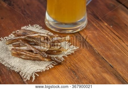 Dried fish in the shape of a straw with beer glass on wooden table. Salted fish delicacies on a table.