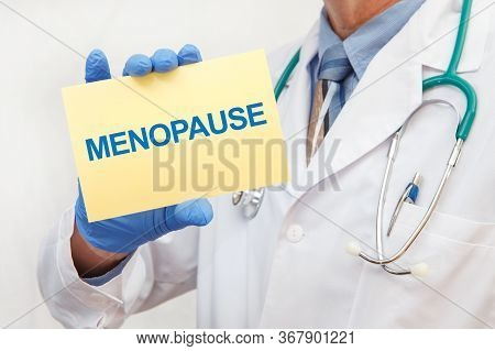 Close-up Of A Male Doctor In Gloves Holding A Sign With The Text Menopause