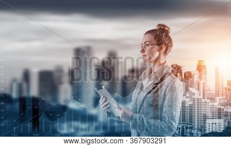 Double Exposure Of Attractive Business Woman Woking On Tablet On Cityscape Background With Infograph