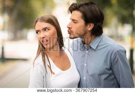 Disgusted Woman Rejecting To Kiss Man Having Bad Date Walking Outdoors In Park. Unanswered One-sided