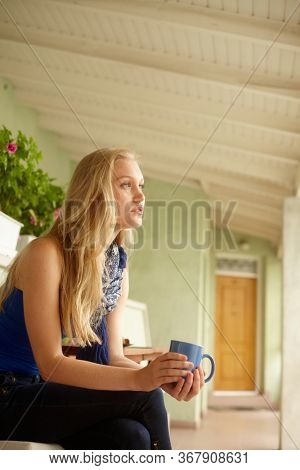 Side view of daydreaming young blonde woman drinking tea in balcony.