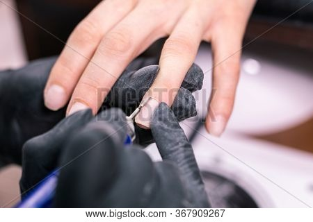 Close-up Professional Beautician Hands Working With Electric Drill On Client Fingernails. Procedure
