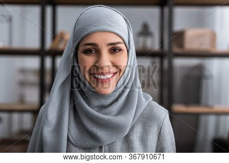 Smiling Muslim Woman In Hijab Looking At Camera In Living Room, Domestic Violence Concept