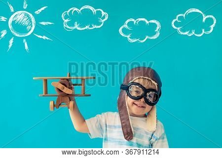 Happy Child Playing With Vintage Wooden Airplane. Kid Having Fun Against Blue Background. Imaginatio