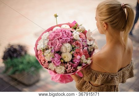 Rear View Of Girl Who Holds Magnificent Bouquet Of Flowers