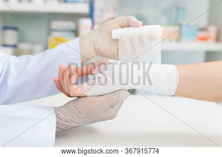 Close-up Hand Wear Medical Gloves  Of Doctor Hand Tying Bandage On The Hand Of Patient In Clinic, Os