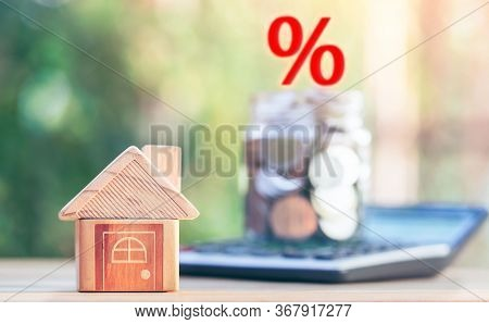 House Placed On The Table. Jar With Money And Interest Illustrations Placed On The Calculator. Conce