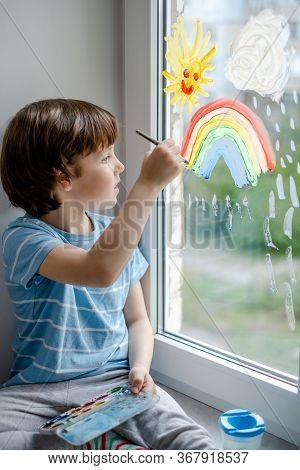 A Little Boy Draws A Rainbow On A Window During A Coronavirus Pandemic.