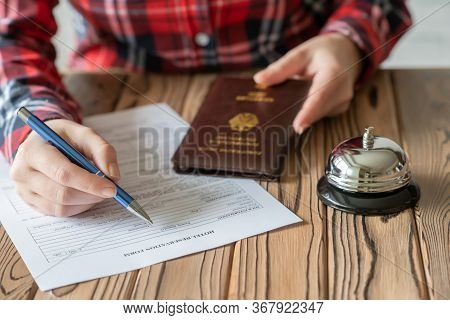 Woman Using Germany Passport Filling Hotel Reservation Form In The Hotel. Silver Vintage Bell On Woo