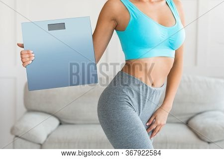 Perfect Weight. Slim Woman Holding Scales After Successful Weight-loss Slimming At Home. Cropped