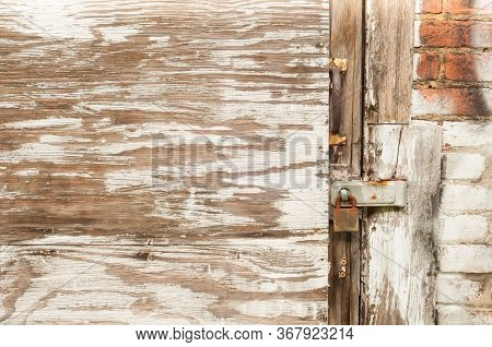 An Old Door Covered With Plywood Boards And Flaking Paint On An Old Urban Warehouse Is Secured By A
