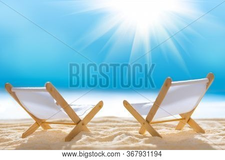 Deck Chairs On Sandy Beach With Blurry Blue Ocean And Sun Beams On Sky. Social Distancing Or Covid-1