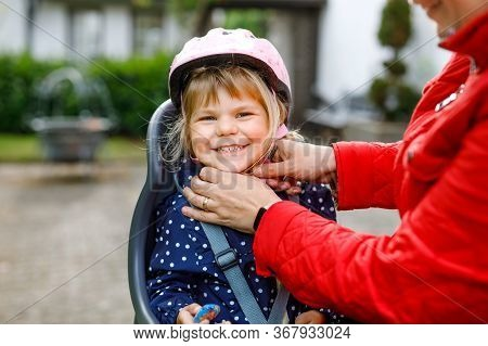 Portrait Of Little Toddler Girl With Security Helmet On The Head Sitting In Bike Seat And Her Mother
