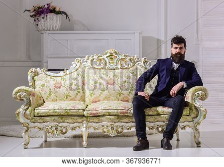 Man With Beard And Mustache Wearing Fashionable Classic Suit, Sits On Old Fashioned Couch Or Sofa. M