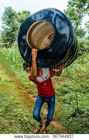 Gorkha,nepal - June 26,2019: Small Nepali Boy Carrying A Heavy Drum On His Shoulder,carrying Heavy L