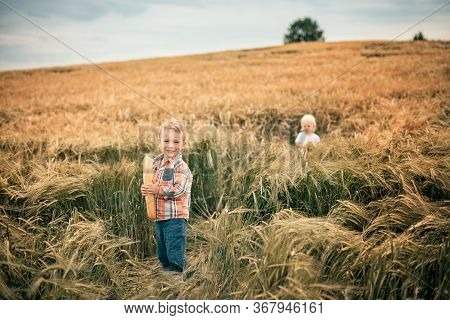 A Blond Boy In An Orange Plaid Shirt And Green Trousers Stands In A Rye Field, Smiles And Holds A Wh