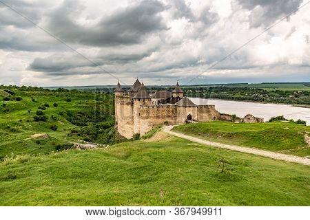 Khotyn Fortress Castle In Ukraine, River On A Background Of Dark Clouds On A Cloudy Windy Day In Sum