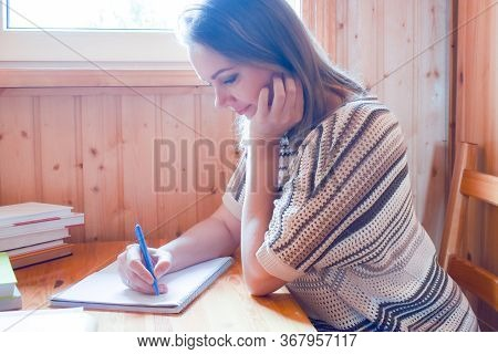 Woman Writing A Text On Paper Behind A Desk In The Room. Hobby Writing And Blogging. A Woman Writer