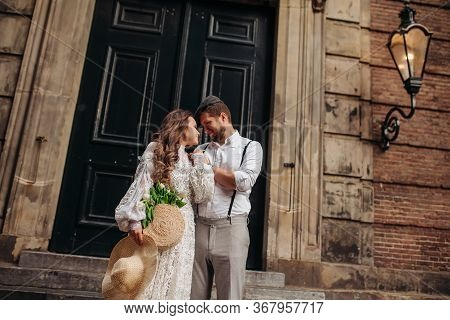 The Groom Gently Embraces The Beauty Bride Under A Streetlight Near An Old Building . He Kisses His