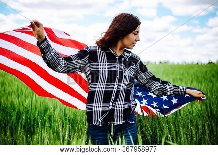Young Woman Waves An American Flag On The Green Wheat Field. Patriotic Holiday Celebration. United S
